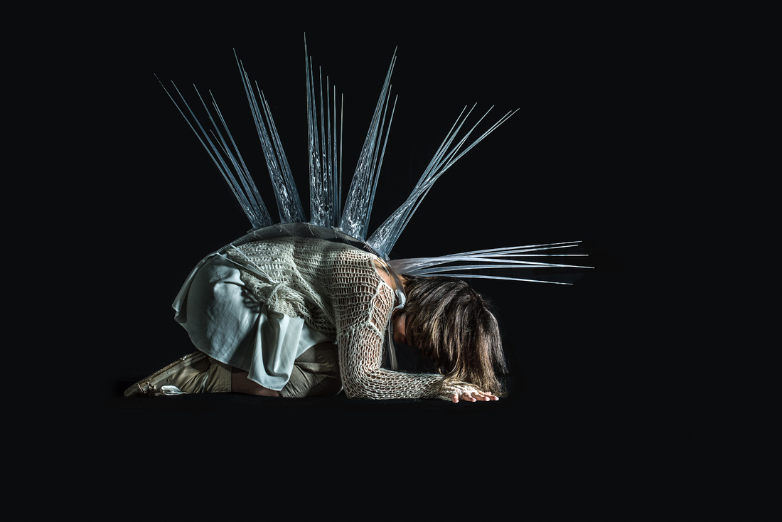 Posion a spike covered woman crouches in the dark