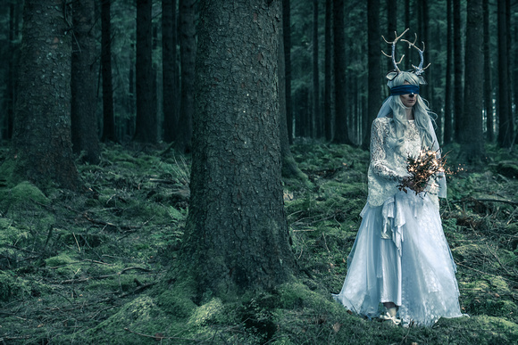 model in white wedding dress with antlers headband